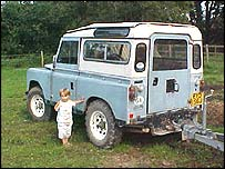 Little boy standing in front of an Old Land Rover