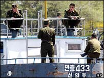 North Korean soldiers relax on a military boat in Sinuiju, opposite the Chinese border town of Dandong