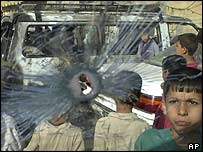 Iraqi children look at a shattered windscreen