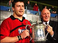 Ballymena captain Bryan Young receives cup from  Ulster Presdient Stephen Hilditch