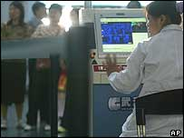 A Chinese health worker sits in front of a machine that monitors the temperature of travellers at Beijing airport on Saturday