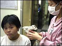 A nurse in a hospital in Taipei, Taiwan, checks a boy's temperature