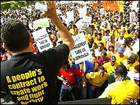 A union official (l) addresses strikers wearing an ANC t-shirt