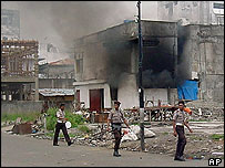 Indonesian police pass burning building in Ambon
