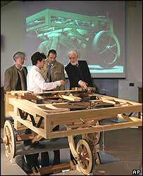 Journalists study the model of the car at Florence's Science Museum
