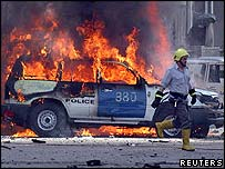 An Iraqi police car on fire after its convoy was attacked