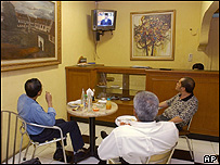 Indonesian men eat dinner while they watch presidential candidate Susilo Bambang Yudhoyono in a televised discussion, Sept. 16, 2004
