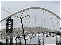 Workers assemble the roof of the main Olympic stadium in Athens