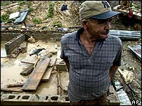 Dominican man surveys his destroyed home