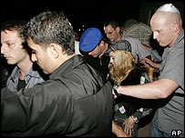 Madonna is surrounded by bodyguards as she leaves the tomb of Rabbi Yehuda Ashlag