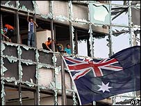 The Australian flag flies as workers remove broken glass from the windows of the buildings surrounding the Australian Embassy in Jakarta