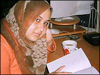 Rana studies a book at her desk