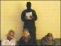 A hostage-taker stands over Briton Ken Bigley and two American captives