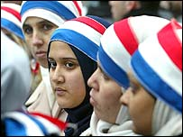 Young women wear headbands in the colours of the French flag as hundreds of Muslims take to the streets in Paris on 17 January 2004