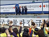 South Korean Red Cross staff wave from aboard a ship loaded with relief goods