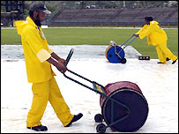 Groundsmen attempt to mop the covers