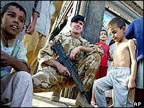 UK soldier surrounded by Iraqi children