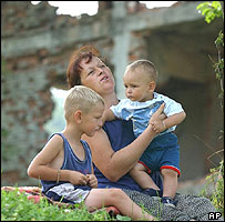 Bosnian Muslim woman Mevlida Osmanovic with sons by a destroyed house near Bratunac, north of Sarajevo