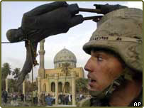 US soldier stands in front of falling statue of Saddam Hussein