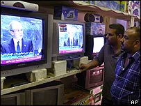 Iraqis in an electronics shop in Baghdad watch President Bush's speech