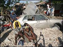 People sit in rubble next to cars destroyed and debris in Gonaives, Haiti