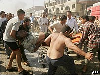 Injured man being taken from Baghdad car bomb site