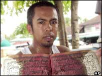 A villager holds up a bloodied book, a remnant of the deadly clash in which 32 militants were killed at the Kreu-Se mosque