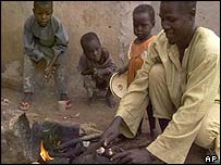 Nigerian family roasting meat