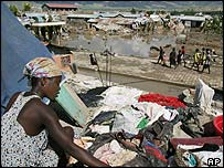 A woman dries out her clothes after floods in Haiti