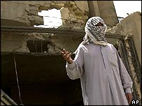 Masked Iraqi showing a damaged house in Falluja