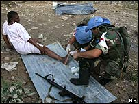 A UN worker treats a woman injured in the Haiti floods