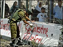 An Israeli soldier removes pro-Palestinian graffiti at Kalandia checkpoint near Ramallah.
