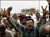 Iraqis near a US checkpoint celebrate the withdrawal