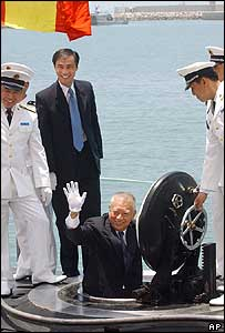 Hong Kong Chief Executive Tung Chee-hwa waves as he comes up through the hatch of a Chinese submarine (30/4/2004)