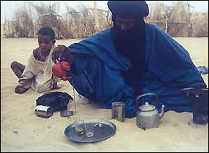 Man pours tea outside his tent in the Mali desert