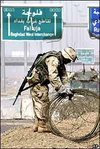 US Army troops clear rolls of razor wire from the main entrance to Falluja