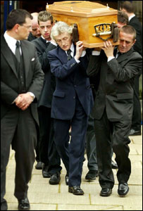 Family and friends carry Kriss Donald's coffin