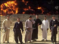 Policemen and private guards stand near a burning oil pipeline in Iraq.