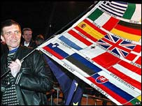 A Polish man with banner showing the flags of all 25 EU members