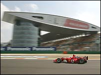 Rubens Barrichello's Ferrari passes the spectacular media centre at the Shanghai track