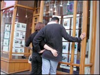 A couple looking at property details in an estate agent's window