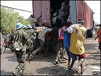 UN peacekeepers try to prevent the looting of a food truck in Gonaives