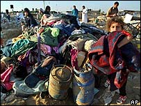 A Palestinian child whose house was demolished holds a blanket
