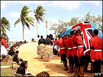 The body of Ratu Sir Kamisese Mara, draped in the Fijian national flag, is carried along a path of tapa mats to his final resting place