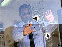 Man points to bullet holes in his office in Yanbu