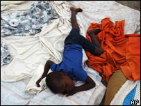 A four-year-old boy sleeps on a rooftop mattress in Gonaives, Haiti