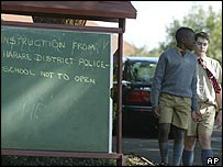 School children from a private school in Harare walk past a sign post stating that the school has been shut down