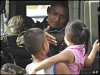 An unidentified Thai soldier reaches out to curious children while on patrol near a train station in Pattani, Thailand, Tuesday, May 4, 2004.