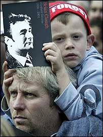 A child carrying a picture of the late Brian Clough