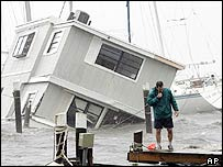 A boat owner walks through the storm to check his boat as a houseboat lies partially submerged in Titusville,  Florida